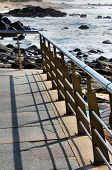 foto of balustrade  - Balustrade forming shadows and the rocky beach - JPG