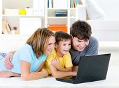 Beautiful happy family with child looking at laptop with cheerful smile - indoors