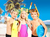 Portrait of the happy children enjoying at beach.  Schoolchild kids standing together in bright colo