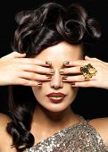 Beautiful  woman with golden nails and creative lipstick. Brunet girl model with style hairstyle on