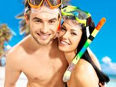 Portrait of  happy fun beautiful couple  at tropical beach with swimming mask on face