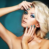 Beautiful blond woman with green nails and glamour makeup of eyes