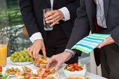 foto of buffet lunch  - Business people eating lunch at office buffet - JPG