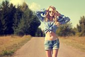 picture of independent woman  - Portrait of Sexy Blonde Woman with Hands behind her Head Walking on Country Road - JPG