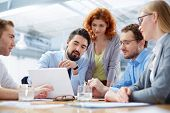 foto of foreground  - Angle view of a business team discussing the future of their company on the foreground  - JPG