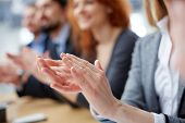 picture of glorify  - Cropped image of a businessperson applauding on the foreground  - JPG