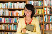 Student - a young woman or girl learning in a library, she proudly holds a couple of books and smili