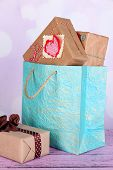 Presents in paper bag on table on bright background