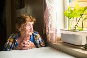 pic of lonely woman  - Lonely old woman sitting by the window in his cottage - JPG