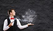 stock photo of fumes  - Young handsome businessman in fumes smoking pipe - JPG