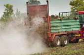 stock photo of fertilizer  - Tractor with trailer fertilizing field with natural manure - JPG