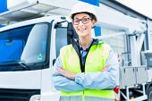 foto of heavy equipment operator  - Female engineer standing in front of truck on building or construction site - JPG