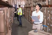pic of warehouse  - Pretty warehouse manager checking inventory in a large warehouse - JPG