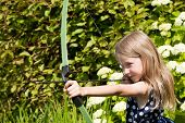 stock photo of bow arrow  - little caucasian girl aiming arrow from big bow closeup on outdoor nature background - JPG