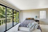 image of master bedroom  - White refreshing master bedroom interior with walkout deck and glass block window - JPG