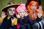 stock photo of warlock  - Portrait of three little girls in Halloween costumes looking at camera with frightening gesture - JPG