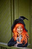 picture of traditional attire  - Halloween girl in special attire looking at camera with smile - JPG