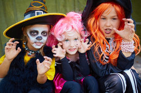 picture of antichrist  - Portrait of three little girls in Halloween costumes looking at camera with frightening gesture - JPG