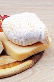 pic of brie cheese  - edam parmesan and brie cheese on wooden platter over wooden table - JPG