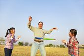 picture of hula hoop  - happy family playing with hula hoops outdoors - JPG