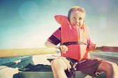 stock photo of life-boat  - Boy rowing a boat on a lake - JPG