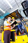 foto of lift truck  - Asian fork lift truck driver discussing checklist with foreman in warehouse  - JPG