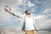 image of cheer up  - Happy young man looking up to the sky holding both hands in the air - JPG