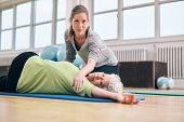 stock photo of physical therapist  - Elderly woman being helped by her personal instructor in the gym for exercising - JPG
