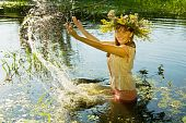 stock photo of undine  - girl in russian traditional clothes playing into water - JPG