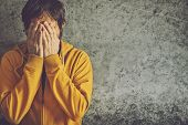stock photo of jacket  - Upset Depressive Adult Man Wearing Yellow Jacket is Crying with his Face Covered - JPG