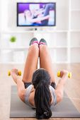 stock photo of training room  - Woman is doing fitness at home on her living room floor while watching and participating in a class - JPG