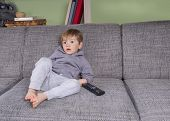 foto of couch potato  - toddler hanging on the couch with a remote control - JPG
