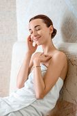 image of sauna woman  - Young woman in white towel sitting and enjoying in Roman sauna - JPG