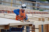 stock photo of purlin  - A builder uses a nail gun to secure timber on the verandah of new building