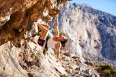 stock photo of cliffs  - Young female rock climber on a cliff face - JPG