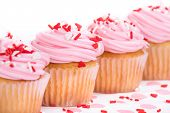 stock photo of sprinkling  - Pink Valentines Day cupcakes with sprinkles - JPG