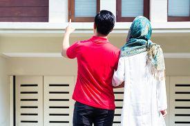 stock photo of muslim man  - Asian Muslim man and woman choosing house  - JPG