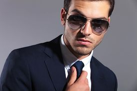 picture of tied hair  - Close up image of a young elegant business man wearing sunglasses - JPG