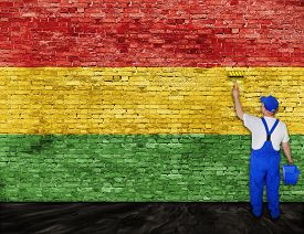 stock photo of reggae  - House painter paints flag of Reggae music on brick wall - JPG