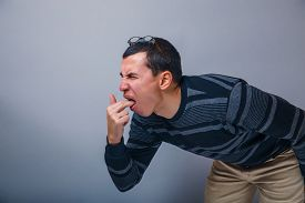 picture of vomiting  - male of European appearance brunette put his fingers in his mouth on a gray background - JPG