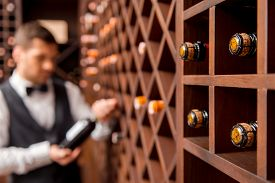 pic of adults only  - Confident male sommelier showing wine bottle and smiling while standing near the wine shelf - JPG