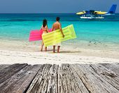 pic of hydroplanes  - Couple with inflatable rafts looking at arrived seaplane on a tropical beach at Maldives - JPG