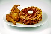 stock photo of fried chicken  - Fried chicken and waffles with maple syrup and butter on a white plate and shot on a white background