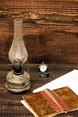 stock photo of petroleum  - petroleum lamp old pocket watch and old book - JPG