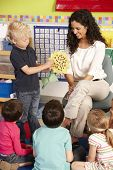 stock photo of teachers  - Group Of Elementary Age Schoolchildren In Class With Teacher - JPG