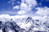 stock photo of snow capped mountains  - Snowy mountains in clouds at sun day - JPG