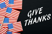 image of give thanks  - The phrase Give Thanks in white text on a blackboard next to flags of the United States Of America - JPG
