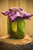 picture of pickled vegetables  - Jar of pickled cucumbers on a wooden stump - JPG