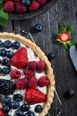 stock photo of tarts  - Homemade tart with fresh berries summer fruit on rustic table - JPG