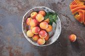 foto of ceramic bowl  - High angle view of fresh sweet apricots in ceramic bowl on a rustic stone surface - JPG